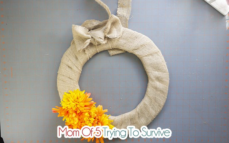 finished wreath wrapped with burlap and orange and yellow flowers hot glued to the bottom of the wreath