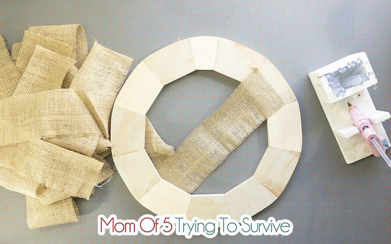 start wrapping burlap around wreath by hot gluing the burlap to the wreath